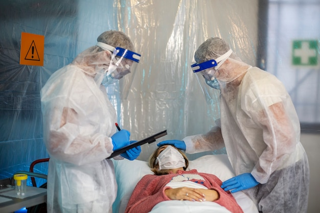 Dos personas cuidan a una mujer con un virus que está acostada en un sofá en un hospital de campaña. virus corona pandémico