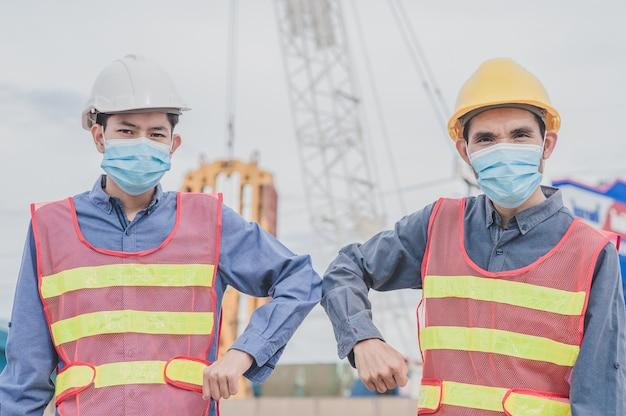 Dos personas con distanciamiento social. ingeniero estrechar la mano sin tocar para prevenir coronavirus