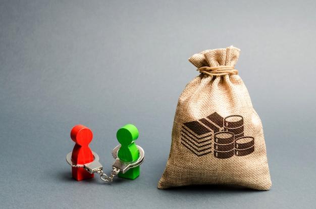 Dos personas están esposadas la una a la otra y se paran cerca de una bolsa de dinero.