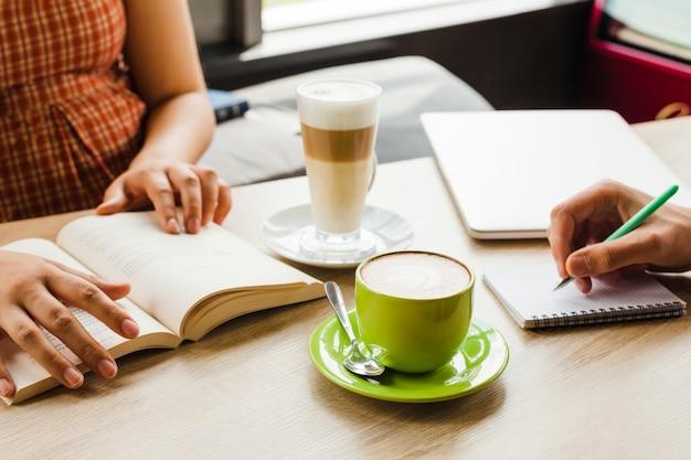 Dos personas estudiando en café con taza de café y café con leche