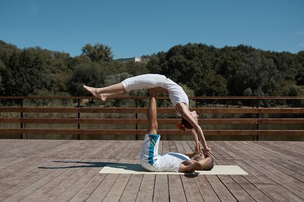Dos personas, hombre y mujer, practicando yoga en el parque