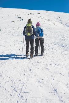 Dos personas irreconocibles caminando por la nieve en la montaña