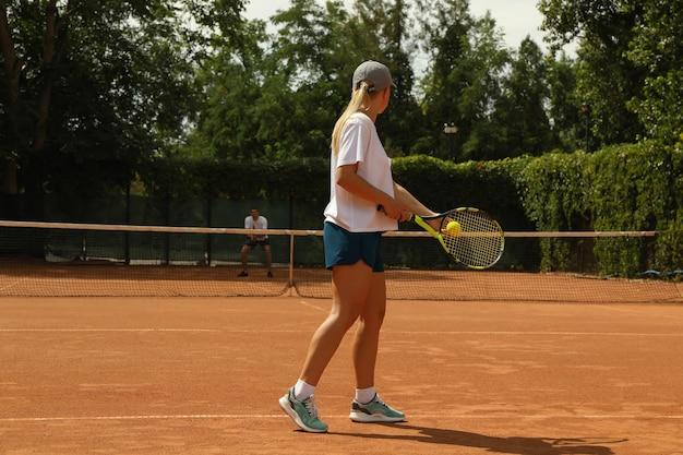 Dos personas jugando al tenis en la cancha de arcilla