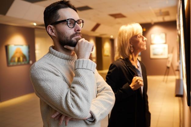 Dos personas mirando pinturas en la galería de arte