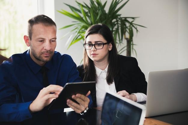 Dos personas en la oficina viendo la tableta