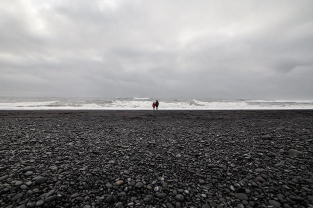 Dos personas en la playa de arena negra de origen volcánico en islandia en un día nublado.