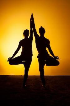Dos personas practicando yoga en la luz del atardecer