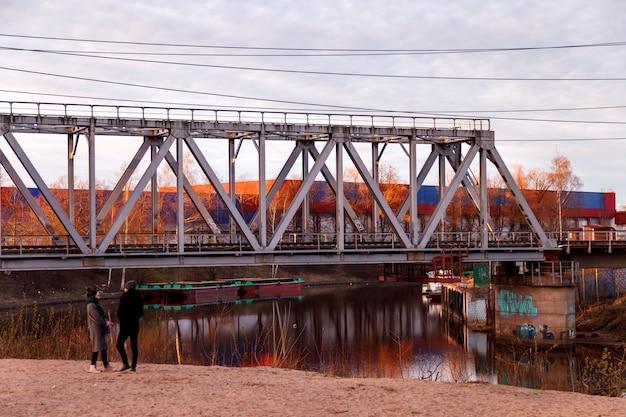 Dos personas en un puente ferroviario en una zona industrial de la ciudad