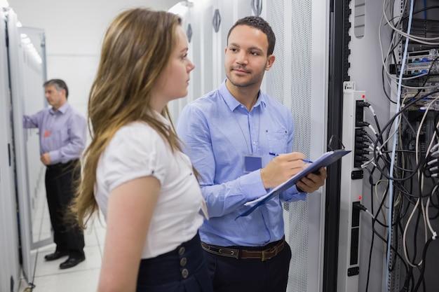 Dos personas revisando servidores con un portapapeles de holding