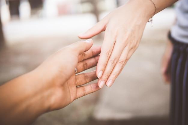 Dos personas tomados de la mano para mayor comodidad. dando una mano amiga.