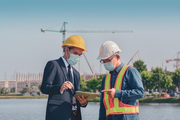 Dos personas trabajando en la construcción del sitio y luego hablando sobre el proyecto de construcción