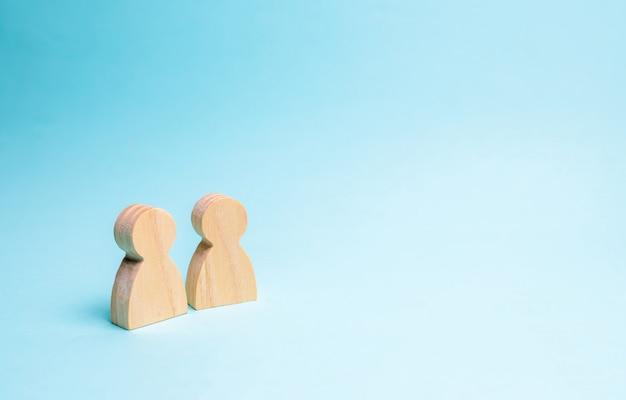 Dos personas se unen y hablan. dos figuras de madera de personas conducen una conversación.