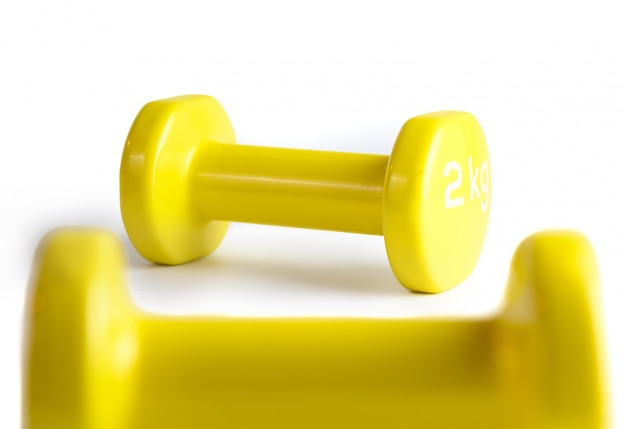 Dos pesas de gimnasia amarillas aisladas en el fondo blanco con el camino de recortes