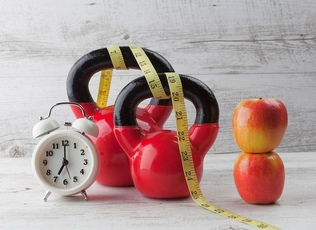 Dos pesas rusas rojas con cinta métrica, manzanas y reloj