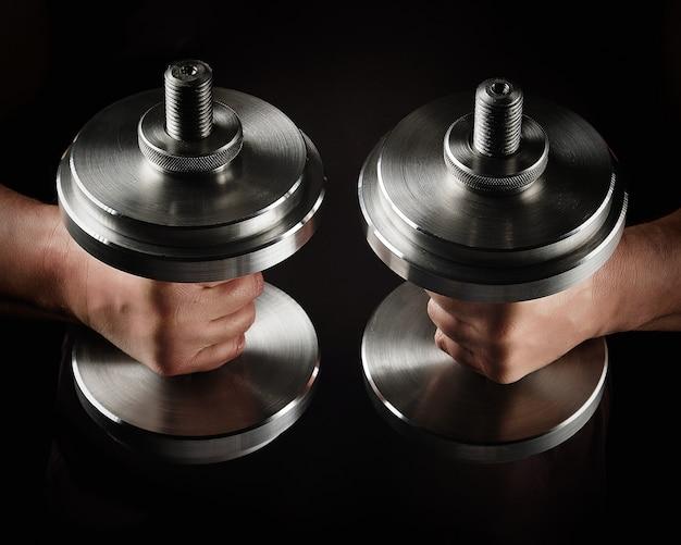 Dos pesas tipográficas de acero en manos masculinas, telón de fondo deportivo