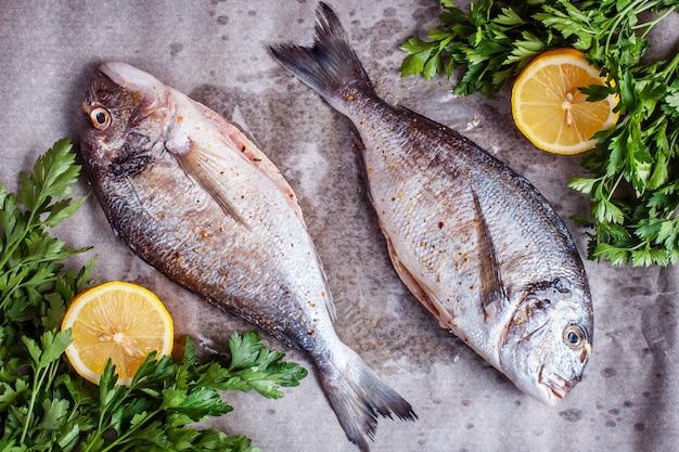 Dos pescados dorados crudos con especias y limón. vista superior