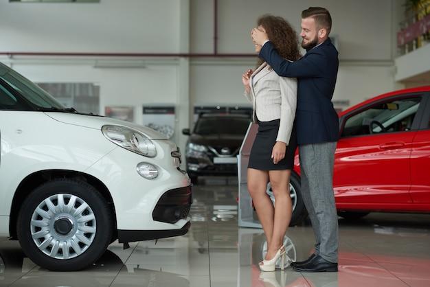 Dos de pie en el centro del coche hombre tomados de la mano en el ojo de la mujer.