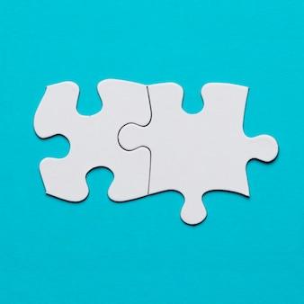 Dos piezas conectadas del rompecabezas blanco sobre superficie azul