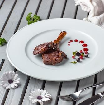 Dos piezas de kebab de costillas de cordero en plato blanco adornado con salsa de bayas