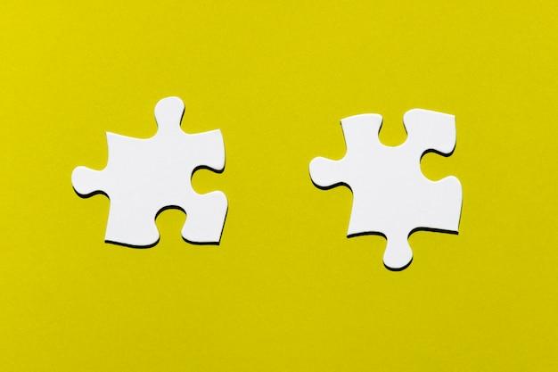 Dos piezas del puzzle blanco sobre fondo amarillo