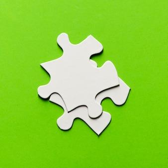 Dos piezas del rompecabezas blanco sobre fondo verde brillante