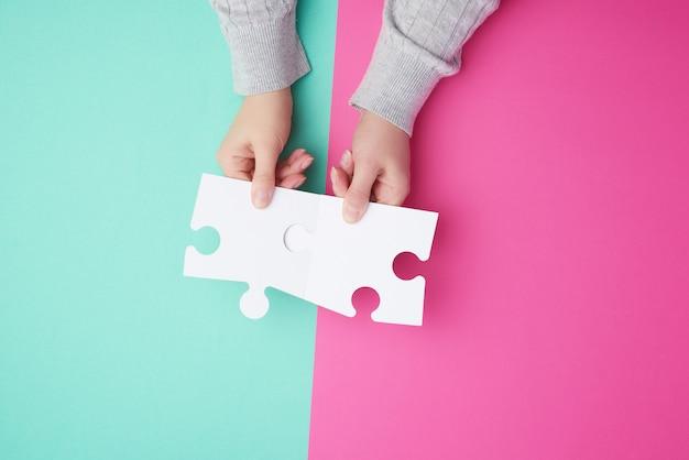 Dos piezas de rompecabezas de papel blanco vacío en manos femeninas, rompecabezas conectado