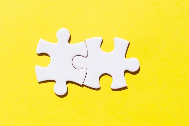 Dos piezas de rompecabezas sobre fondo amarillo iluminante