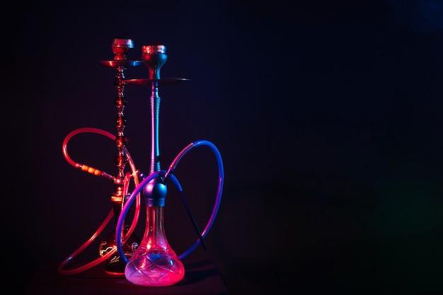 Dos pipas de agua con luces de neón rojas y azules sobre la mesa en el café del salón sobre un fondo oscuro