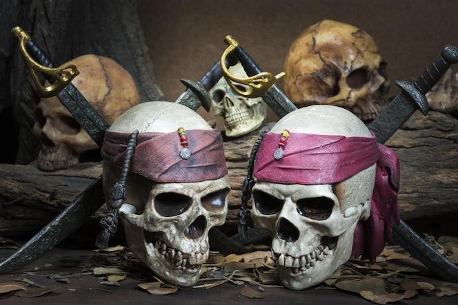 Dos piratas cráneo más de tres cráneo humano en el bosque