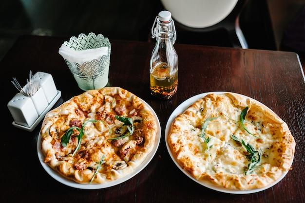 Dos pizza italiana cuatro quesos con carne de rúcula en un mostrador de madera marrón