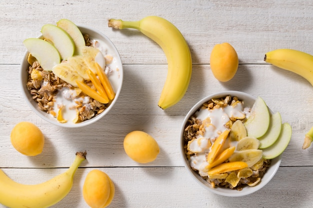 Dos platos con avena y tazas de copos de maíz y arroz inflado sobre un fondo blanco de madera