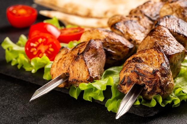 Dos porciones de shish kebab en una placa de piedra con ensalada, pan de pita en rodajas, tomates cherry