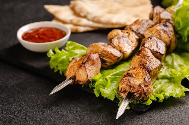 Dos porciones de shish kebab en una placa de piedra con ensalada