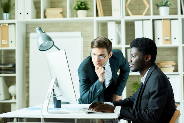 Dos profesionales de negocios usando la computadora