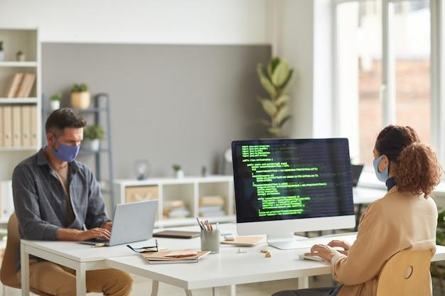 Dos programadores con máscaras protectoras que programan programas blandos y escriben guiones en computadoras en la mesa de la oficina de ti