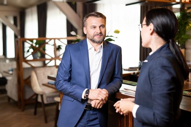 Dos propietarios contemporáneos de un restaurante moderno que discuten los puntos de trabajo en la reunión por barra de bar