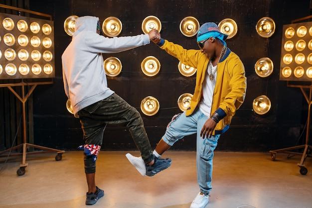 Dos raperos negros con gorras abrazándose en el escenario