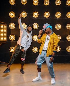 Dos raperos negros con gorras, actuación de baile en club, escenario con focos