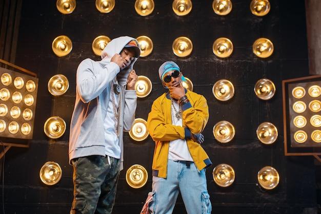 Dos raperos negros con gorras en el escenario con focos