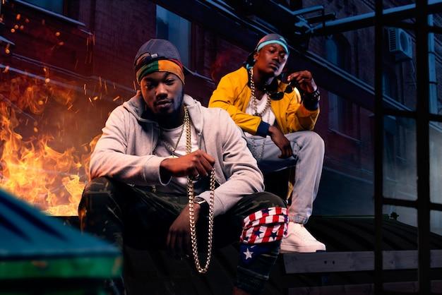 Dos raperos negros con gorras sentados junto al fuego, calle de la ciudad de noche