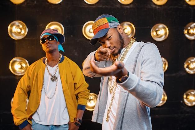 Dos raperos negros en mayúsculas, artistas en el escenario con focos.