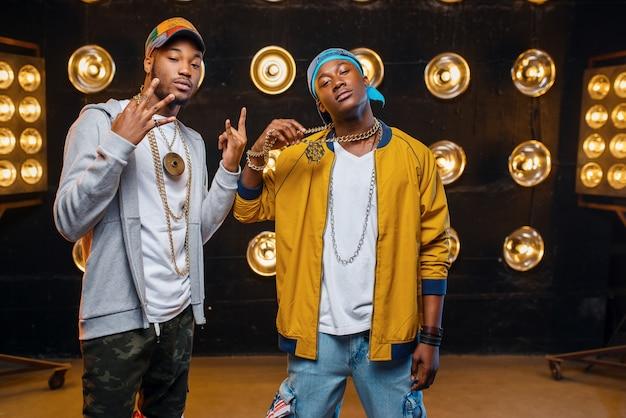 Dos raperos negros en mayúsculas, artistas posan en el escenario.