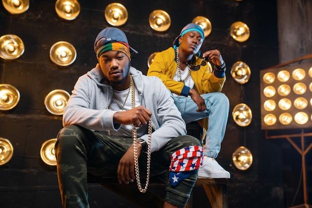 Dos raperos negros sentados en los escalones