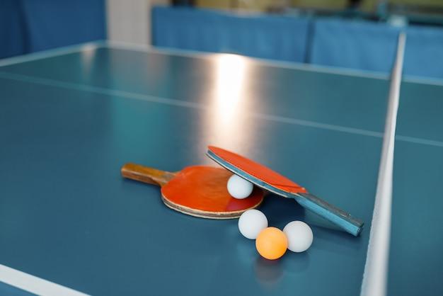 Dos raquetas de ping pong y pelotas en la mesa de juego con net