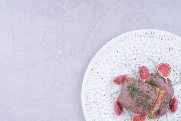Dos rebanadas de filete de carne con higos en una placa blanca.