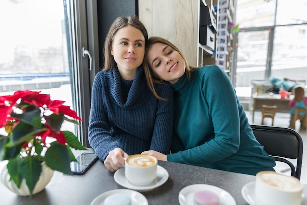 Dos riendo abrazando a mujeres jóvenes sentados a la mesa en la cafetería.