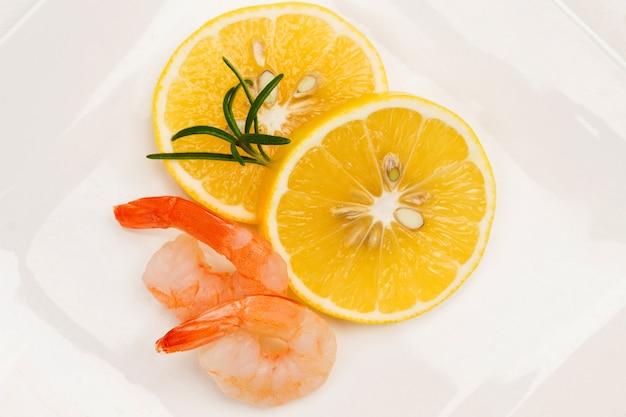 Dos rodajas de limón y dos camarones en un plato blanco. endecha plana