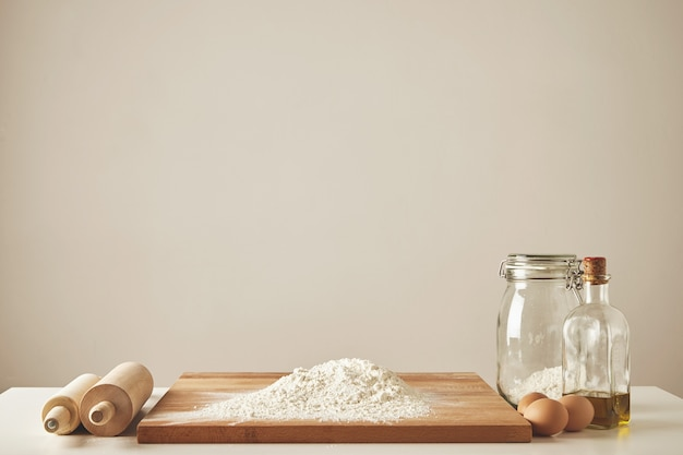 Dos rodillos de madera, aceite de oliva virgen extra, tarro transparente y tabla de cortar de madera con harina blanca, huevos de pollo aislados. todo preparado para hacer masa.