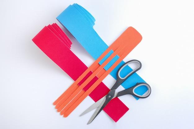 Dos rollos de cinta de kinesiología para atletas y tijeras sobre fondo blanco.