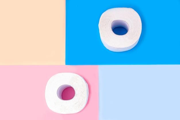 Dos rollos de papel higiénico blanco sobre fondo de color. copiar espacio para texto, plano. productos de higiene
